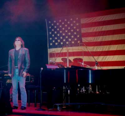 Ronnie, standing in front of American Flag at end of show